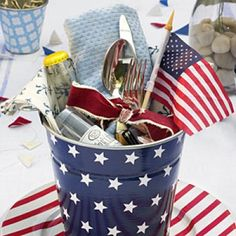 Corral napkins, flatware, bottled drinks, and other party supplies at each place setting in a star-covered metal pail that can double as a take-home favor