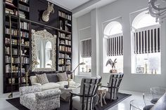 A generous dose of funky flair starts in the living room with a timeless, yet playful space with a wink of whimsy. A crisp black-and-white theme with brass accents lays a classic foundation, while lighthearted details provide a dash of spice: the zebra head perched above an antique carved-wood mirror, a hoofed side table and a brass hand that appears to reach out from a rock-shaped cocktail table.