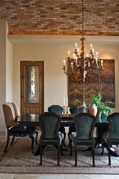 Off the foyer is the formal dining room. Curved-backed chairs and a long wooden table are paired with an ornate chandelier and artwork. The ceiling features exposed brick, while the tile floor is grounded with a neutral area rug.
