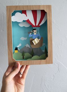 """The Roadside Projects Shadow Box Kit has all the materials you need to create your own three-dimensional cut paper masterpiece. With basic art supplies, you'll learn a fun and unique form of papercraft.    KIT INCLUDES: wood shadow box frame - size: 6"""" x 8"""" x 2"""" satin ribbon for hanging  archival colored card stock + extra for customizing  templates + extra for customizing  transfer paper  easy-to-follow, illustrated instructions    Personalizing your Balloon Adventure shadow box is easy…"""