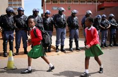 School girls walk past riot police standing guard outside Hillbrow magistrate court during an appearance of students who were arrested during a protest demanding free education at Johannesburg's University of the Witwatersrand, South Africa, Oct. Schools Around The World, Around The Worlds, University Of The Witwatersrand, Walk To School, First Day Of Class, Riot Police, Girls Uniforms, School Uniforms, Women In Leadership