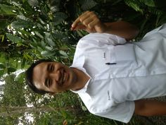 Our wonderful (and funny) guide for the day, Anom, holding a coffee bean.