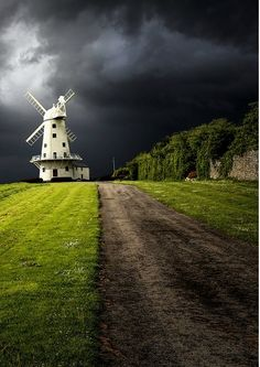storm clouds hover over windmill home on a lone country road