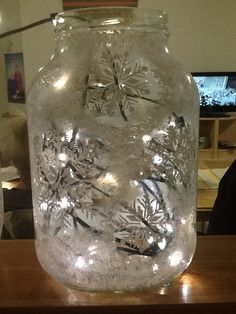 Lights in glass jar. I painted white snowflakes on it.