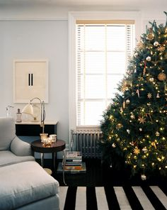 Holiday Decor Photo - A Christmas tree beside a gray chair and ottoman and a black-and-white-striped rug