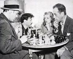 "Lauren Bacall gives chessmaster Herman Steiner ""the look"" while Charles Boyer and Humphrey Bogart finish a game between takes of ""Confidential Agent"" (1945) in which Boyer was starring. The scene is Boyer's dressing room at Warner Bros. Studio."