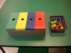 Sort by color.  Just get an old shoe box and make the holes slightly larger than the colored objects.  Cover the box with colored paper and clear tape. I inserted dividers inside the box so I could check work upon completion. I bought the cylinders at the dollar spot in Target.