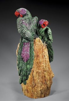 <b>FINE AND LARGE PAIR OF RUBY IN ZOISITE PARROT CARVINGS</b></i></u> <br  /> <i>Carved by Luis Alberto of Peru</b></i></u> <br  /> The beautiful forest green zoisite used for this carving has been artfully deployed to give this large pair of birds a natural patterning of black specks and stripes, dotted with patches of dramatic purple-red ruby inclusions and separate sections of ruby applied to form the eye feathers. With silver legs and taloned feet, the birds are mounted on a characterful…