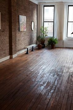 Wood floor + exposed brick walls.