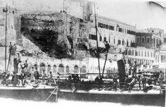 """Μια φωτογραφία του Π. Διαμαντόπουλου, μετά το 1897, που κάηκε το Διοικητ'ηριο (διακρίνεται σωρός από τα """"αποκαϊδια). Δεξιά και πάλι τα υπολείμματα του Palazzo και το Σχολείο της Μουσουλμανικής Κοινότητας. Ο μικρός όρμος έχει μπαζωθεί και στην πλατεία που σχηματίστηκε έχει κτιστεί το Τελωνείο και η Τράπεζα Χανίων, ενώ μπροστά από το μεταγενέστερο τείχος έχουν κτιστεί αποθήκες του Λιμανιού ( Creative Christmas Trees, Tree Identification, Greece, Painting, Vintage, Crete, Painting Art, Paint, Vintage Comics"""
