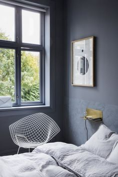 Inside the couple's Oslo apartment and shop. A diamond-shaped chair designed by Harry Bertoia for Knoll sits by a bedroom window.