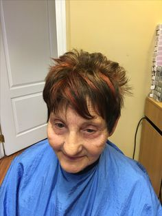 White hair colored brown with red copper highlights. Cut short with texture and style