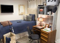 Guy's simple yet functional dorm room - blue bed spread, blue and beige rag rug, gray washed desk cubby, beige upholstered headboard, reclaimed wood state art