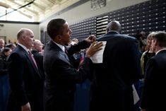President Barack Obama leans on the back of personal aide Reggie Love to sign a note after a town hall meeting at Nashua High School in Nashua, N.H., Feb. 2, 2010.