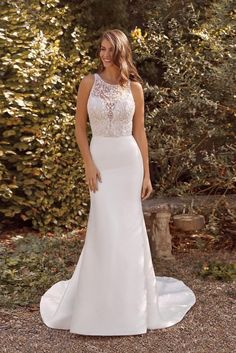 This fit and flare gown is elegant and sophisticated. It features a hand beaded bodice with a Jewel neckline and a clean stretch Mikado skirt with buttons to the end of the train. The delicate crisscross straps on the back complete the look.