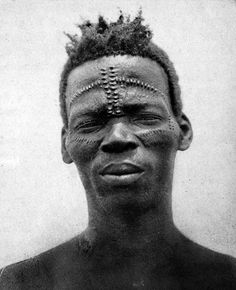 Africa | Portrait of a man from the Congo with scars on his face. || Vintage print dated 1925.