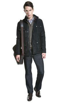 Camisa xadrez azul, tricô khaki escuro com couro no decote, jaqueta de nylon marinho, calça jeans raw, bota de couro e pasta messenger.