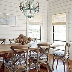 Coastal dining room with beaded-glass chandelier, shiplap walls, wooden floors, and framed nautical print.