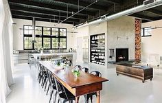 Long tables, polished concrete, fireplace. Open style living
