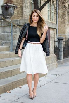 cute work outfits, white flared knee length skirt, worn by woman with blonde ombre hair, with black t shirt, and leather jacket over her shoulders