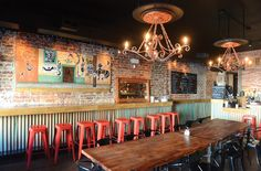 """Tio Pablo's murals are inspired by Mexican folk sculptures called alebrijes. Artist Linda Lauby says she combined motifs to create a """"sort of tattooed street scene,"""" with chandeliers and décor made from objects that sat in her workshop for years. """"We wanted everything to be warm and inviting,"""" she says, """"yet with a bit of an edge. All the masks are authentic Central American masks, and some are quite old. I have a huge reverence for items that endure."""" - SCOTT ELMQUIST"""