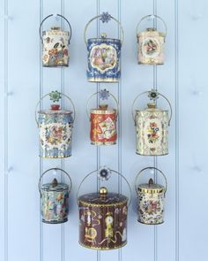 Blue Wall - Suspended from wooden pegs tipped with 1940s tin tiebacks is a bevy of covered tin pails from the 1950s and '60s, some lithographed with scenes or birds, a la hand-painted Continental porcelains, others with bouquets or all-over prints.
