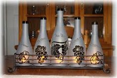 Wine bottles cut and frosted with candles.