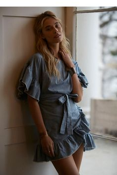 Wrapped In Ruffles Dress | Apron-style chambray wrap dress featuring ruffled sleeves and hem. Button closure at the back for an easy fit. Fun and flirty silhouette.