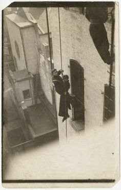 Djuna Barnes and unidentified fireman, dangling from a rope beside a building, October 1914. Gelatin silver photograph. Djuna Barnes Papers, Special Collections, University of Maryland Libraries