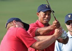 United States team player Tiger Woods, right, helps team player Steve Stricker with his swing before a team photo at the Presidents Cup golf tournament
