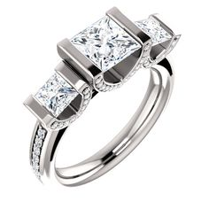 Three princess-cut diamonds are bar-set in U-shaped settings adorned with small round white diamonds in profile on this engagement ring available in white gold, platinum or sterling silver.  Ref# STU-122597.  Goldex Fine Jewelry ~ (323) 726-7181.