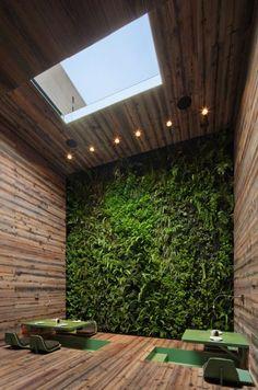 Bijzondere ruimte, veel hout en een planten-wand, zitjes verzonken in de vloer
