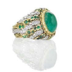 BUCCELLATI EMERALD AND DIAMOND 18K GOLD RING - Oval cabochon cut emerald, 8.35 x 4.5 x 11.59 mm. by formula, in textured gold bezel radiating white gold diamond leaves and yg. emerald leaves. RBC diamonds approx. 1 cts. TW, ca. 1970. Signed GM Buccellati, for Gianmaria Buccellati, Italy, 18k. Size 7 1/2. 12.3 dwt. Original Box