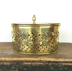 This vintage lidded brass box is highly decorative with its oval shape and cutwork design. Suitable for storing any number of small items, it would be perfect for potpourri with its openwork.  It has become very slightly misshapen, though not to the extent that the lid no longer fits, and there are some small areas of discolouration to the metal due to age and wear, as can be seen in the second picture. However, as with most vintage items this patina just adds to its appeal.     Please…
