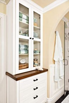 Seeded-glass doors and a wood counter top give this guest-bath storage unit a furniture-like feel. Photo: Mark Lohman | thisoldhouse.com |