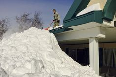 A New York National Guard airman assists in snow removal efforts from the roof of the Eden Heights Assisted Living Facility in West Seneca, N.Y., Nov. 19, 2014. The airman is assigned to the 107th Airlift Wing based in Niagara Falls, N.Y.