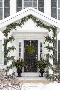 Christmas entry with black door and green garland. DIY winter urns to accent Christmas entry with black door and green garland. DIY winter urns to accent Christmas Porch, Magical Christmas, Noel Christmas, Outdoor Christmas Decorations, Green Christmas, Winter Christmas, Christmas Lights, Winter Porch, Christmas Entryway