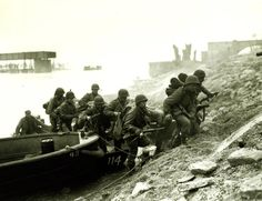 Crossing the Rhine, 1945. Soldiers of the U.S. Army 7th Infrantry Regiment, 3rd Division, leave the assault boat that took them across the Rhine River, 26 March 1945. They climb the river's enemy-held east bank, next to a destroyed bridge in the Frankenthal area. Most of these men are armed with M-1 carbines. Photograph by T/5 Joseph A. Bowen. US Army Photograph, SC 204081