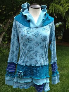 Upcycled Recycled Elf HoodieTunic in Cotton Size Small to Medium Aqua, Teals, Blues, Prints This up cycled tunic hoodie is made from at least 5 different garments. It includes a floral print, a celestial star print, solids and stripes. The flower pin is removable. It is mostly