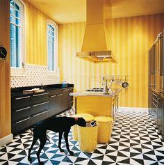 Cocina - AD España, © Daniel Riera En la cocina, el suelo y la pared del lavadero están hechos en imitación a la baldosa hidráulica típica de las casas catalanas, pero reinterpretados en mármol y madera. Las paredes amarillas están pintadas con unas franjas mates y otras brillantes.
