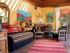 The outdoor living room (sala abierto) is an essential room in this Spanish-inspired home, blending the indoor space with the outdoors. The courtyard is placed at the center of the home, a traditional Old World Spanish design. Carole Meyer chose vibrant reds, greens, yellows and turquoise, colors which represent the lively Mexican culture. The cushions on the Spanish-style hacienda chairs are upholstered in black Sunbrella fabric for practical reasons, and all the bright, colorful paintings…