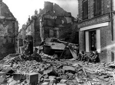 American troops rest in the rubble of Argentan next to a knocked-out Panther medium tank and wonder why their offensive to seal off the enemy escape routes has ground to a halt.