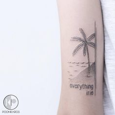 """Everything irie"" and palm tree tattoo on the back of the left arm."
