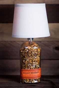 Empty Bulleit Bourbon Bottle repurposed into a lamp. Handcrafted lamp with tan linen shade, brown river rocks, and turn key switch Old Liquor Bottles, Lighted Wine Bottles, Antique Bottles, Vintage Bottles, Bottle Lights, Vintage Perfume, Antique Glass, Perfume Bottles, Diy Bottle Lamp