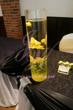 #Attractive #submerged #centerpiece of #yellow #orchids and #green #berries in a #cylinder #vase looks amazing on the #black and #white #receiving #table.