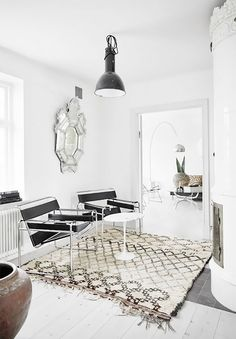 Living space with a vintage mirror, a large industrial light, and matching leather chairs