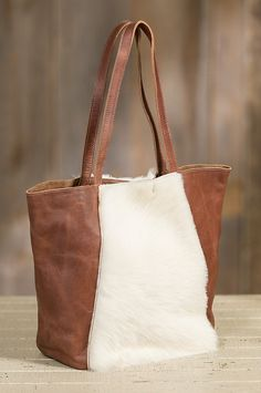 Premium Italian bovine leather is lavishly accented with a textured panel of soft sheepskin fur on the front and back, for an eye catching design that's fun to touch. Made in Canada.