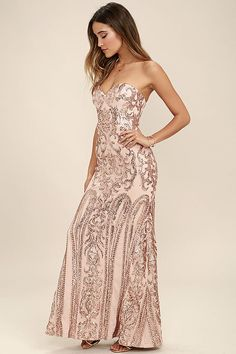 The Bariano Rebecca Rose Gold Strapless Sequin Maxi Dress is sure to make you the belle of the ball! A breathtaking rose gold sequin pattern covers a strapless, sweetheart neckline with princess seams, lightly padded cups, hidden boning and no-slip strips. Fitted bodice gives way to a flaring mermaid maxi skirt. Hidden back zipper and clasp.