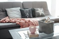 Cocoa with marshmallows and book and knitted basket with yarn and needles on coffee table. Warm pompon blanket and cushions on the sofa. Still life photo of nordic interior details. Pink Coffee Mugs, Miracle Morning, Nordic Interior, How To Wake Up Early, Living Room Colors, Hygge, Modern Decor, Decor Styles, Relax