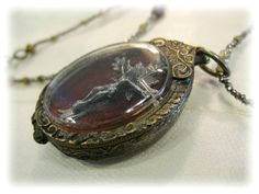one side of the double locket...antique silk velvet on the inside with an old cross...